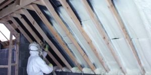 Guy doing spray foam insulation in an attic